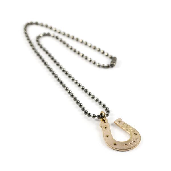 Gargantilla Herradura compuesta de cadena militar con baño gris titanio y herradura de bronce bañada en oro rosado 24K.